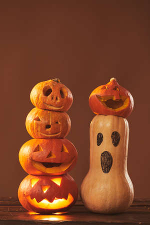 Still life composition studio shot of ripe pumpkins carved and gourd painted for Halloween party decoration, brown background