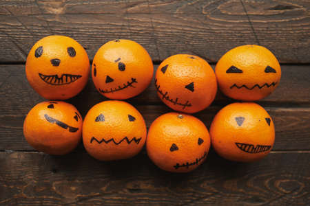 Group of orange tangerines with jack o lantern faces drawn on them lying on dark brown wooden table, flat lay