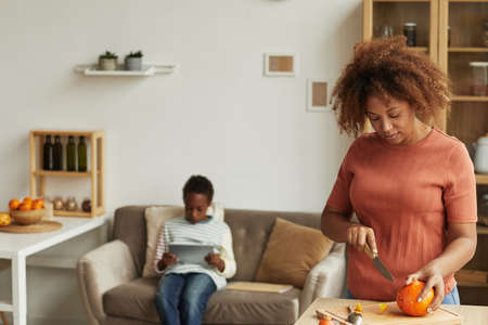 Young adult African American woman carving pumpkin for Halloween party while her son sitting on sofa and watching something on digital tablet