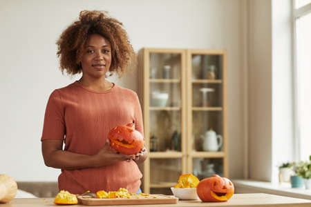 Beautiful African American woman wearing casual outfit standing at kitchen table holding pumpkin carved for Halloween