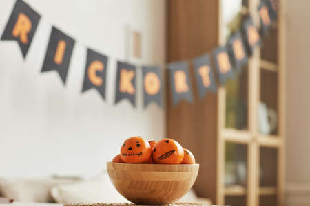 Horizontal no people shot of fresh tangerines with Jack O Lantern faces drawn on them lying in wooden bowl for Halloween party 写真素材