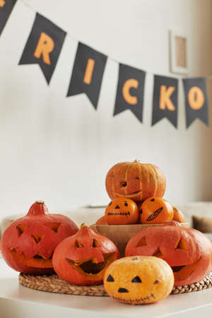 Group of carved pumpkins and tangerines with spooky faces prepared for Halloween party at home, no people shot 写真素材