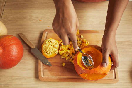 Top-down shot of womans hands scooping seeds and fibres out of small ripe pumpkin using spoon 写真素材