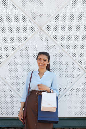 Vertical waist up portrait of young woman holding shopping bags and smiling at camera while standing outdoors by mall, copy space above