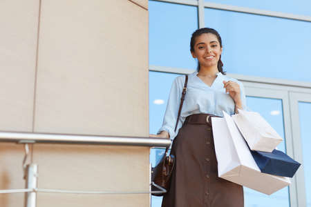Waist up portrait of young woman holding shopping bags and smiling at camera while standing outdoors by mall entrance, copy space Stockfoto