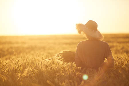 Back view portrait of young woman walking across golden field holding heap of rye and wearing straw hat lit by sunset light, copy space