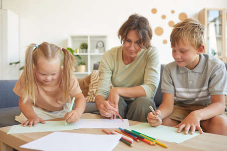 Portrait of cute blonde girl with down syndrome drawing with mother and brother together in home interior Standard-Bild