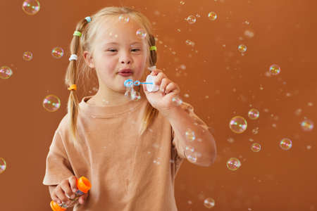 Waist up portrait of cute girl with down syndrome blowing bubbles while posing against brown background in studio, copy space