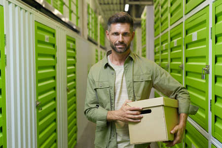 Waist up portrait of handsome man holding cardboard box standing in self storage facility and looking at camera, copy space