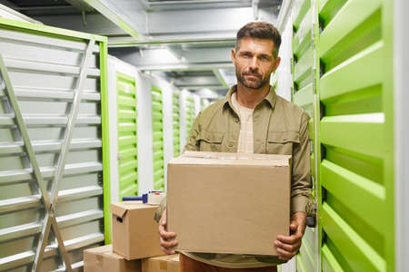 Waist up portrait of handsome bearded man carrying cardboard box looking at camera while standing in self storage facility, copy space
