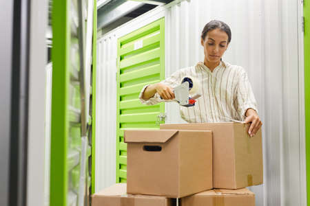 Portrait of young woman packing boxes with tape gun while standing by self storage unit, copy space Archivio Fotografico