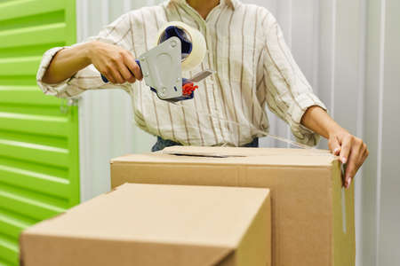 Cropped portrait of unrecognizable young woman packing boxes with tape gun while standing by self storage unit, copy space Standard-Bild