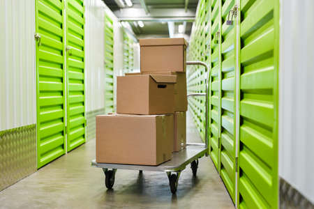 Background image of cart with cardboard boxes in empty hall of self storage facility, copy space