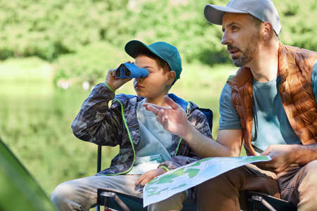 Portrait of teenage boy looking in binoculars while enjoying camping trip with father, copy space