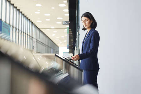 Side view portrait of contemporary Middle-Eastern businesswoman swiping phone while passing turnstile gate in airport or office building, copy space