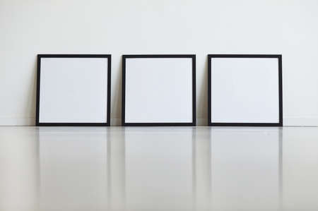 Background image of three identical black frames set against white wall in row at art gallery, copy space Foto de archivo