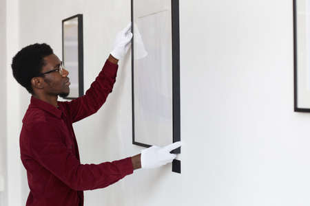 Side view at African-American man hanging blank frames on wall while planning art gallery or exhibition, copy space