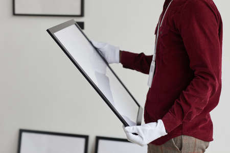 Cropped portrait of unrecognizable man wearing gloves holding painting frame while standing against white wall in art gallery, copy space