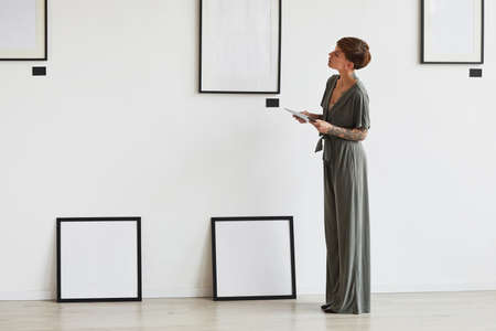 Graphic full length portrait of elegant female art gallery manager looking at frame setting while planning exhibition or event, copy space