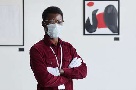 Waist up portrait of African-American man wearing mask looking at camera while standing with arms crossed against modern graphic paintings in art gallery, copy space
