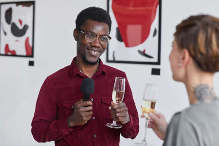 Waist up portrait of smiling African-American man holding microphone and interviewing guests at art gallery opening