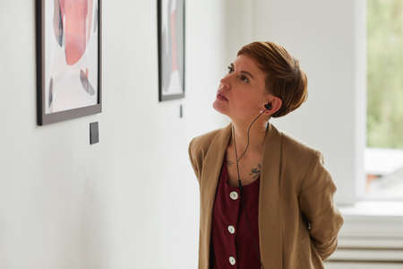 Waist up portrait of tattooed young woman looking at paintings and listening to audio guide at modern art gallery exhibition, copy space Foto de archivo