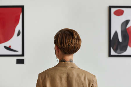 Graphic back view portrait of tattooed young woman looking at paintings and listening to audio guide at modern art gallery exhibition, copy space