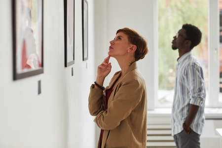 Side view portrait of elegant young woman looking at paintings while exploring modern art gallery exhibition, copy space