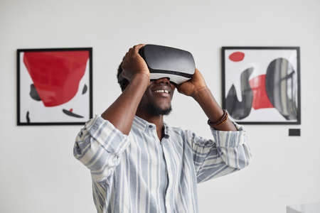Graphic waist up portrait of smiling African-American man wearing VR gear while enjoying immersive experience at modern art gallery exhibition, copy space Stock Photo
