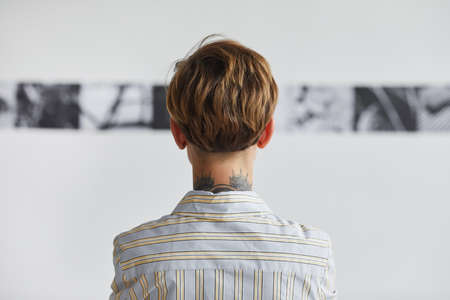 Graphic back view portrait of tattooed young woman looking at paintings at contemporary art exhibition, copy space