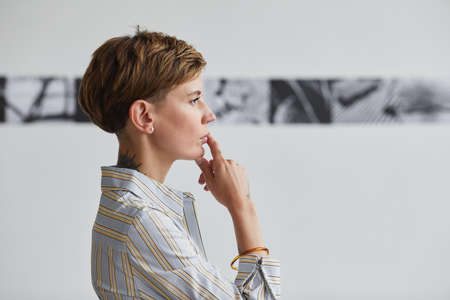 Graphic side view portrait of tattooed young woman looking at paintings at contemporary art exhibition, copy space