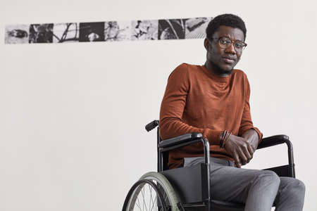 Minimal portrait of young African-American man using wheelchair and looking at camera while posing against white wall in modern art gallery, copy space