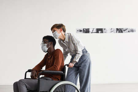 Minimal portrait of African-American man using wheelchair and looking at paintings in modern art gallery with young woman helping him, both wearing masks, copy space