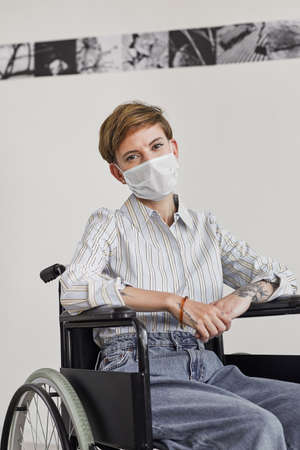Vertical portrait of young woman using wheelchair and wearing mask while looking at camera against white wall in modern art gallery Banque d'images