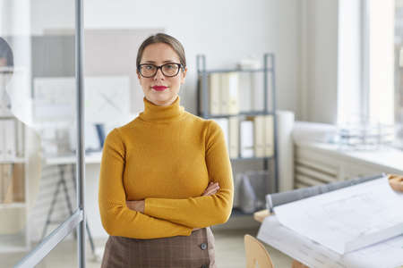 Waist up portrait of confident female architect looking at camera and smiling while standing with arms crossed by drawing desk in office, copy space
