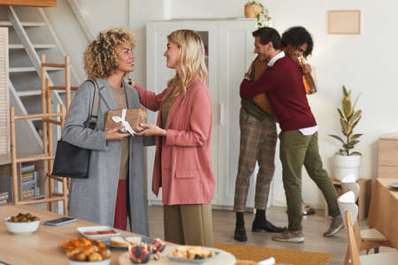 Group of elegant adult people greeting each other and exchanging gifts while welcoming guests at dinner party indoors