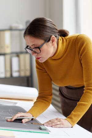 Vertical portrait of adult female architect drawing blueprints and plans while working at desk in office