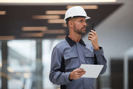 Waist up portrait of handsome mature worker speaking by walkie-talkie while supervising work at construction site or in industrial workshop, copy space 版權商用圖片