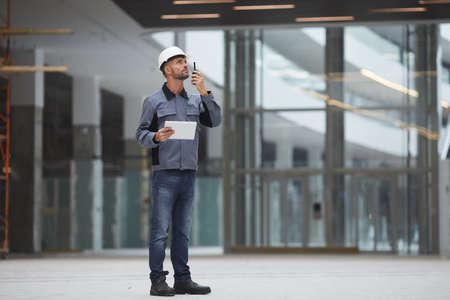Full length portrait of mature worker speaking by walkie-talkie while supervising work at construction site or in industrial workshop, copy space 版權商用圖片