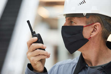 Side view portrait of mature worker wearing mask and speaking by walkie-talkie while working on industrial site, copy space