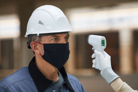 Portrait of mature worker wearing mask and waiting to measure temperature with contactless thermometer at construction site, corona virus safety Stockfoto