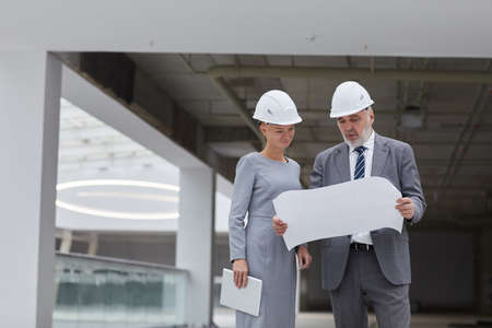 Waist up portrait of smiling businesswoman looking at plans at construction site indoors, copy space
