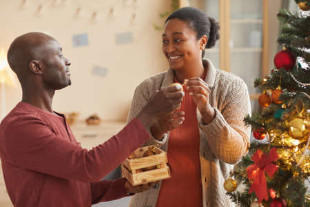 Waist up portrait of loving African-American couple decorating Christmas tree with together while enjoying holiday season at home