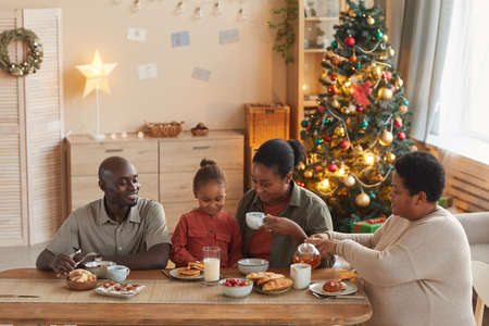 Warm toned portrait of happy African-American family enjoying tea and snacks while celebrating Christmas at home in cozy home interior, copy space
