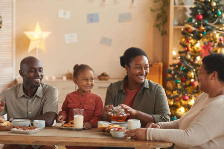 Warm toned portrait of happy African-American family enjoying tea and snacks while celebrating Christmas at home in cozy home interior