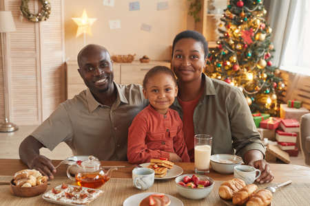 Portrait of happy African-American family enjoying tea and sweets while celebrating Christmas at home in cozy home interior Stockfoto