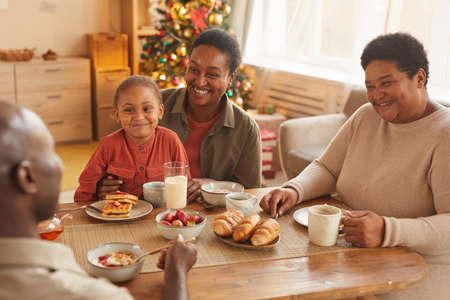 Warm toned portrait of happy African-American family enjoying tea and snacks while celebrating Christmas at home