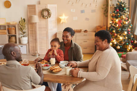 High angle portrait of happy African-American family enjoying tea and snacks while celebrating Christmas at home