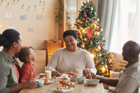 Warm toned portrait of big African-American family enjoying tea and snacks while celebrating Christmas at home