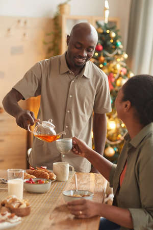 Vertical portrait of smiling African-American man pouring tea for wife while enjoying Christmas dinner at home Foto de archivo